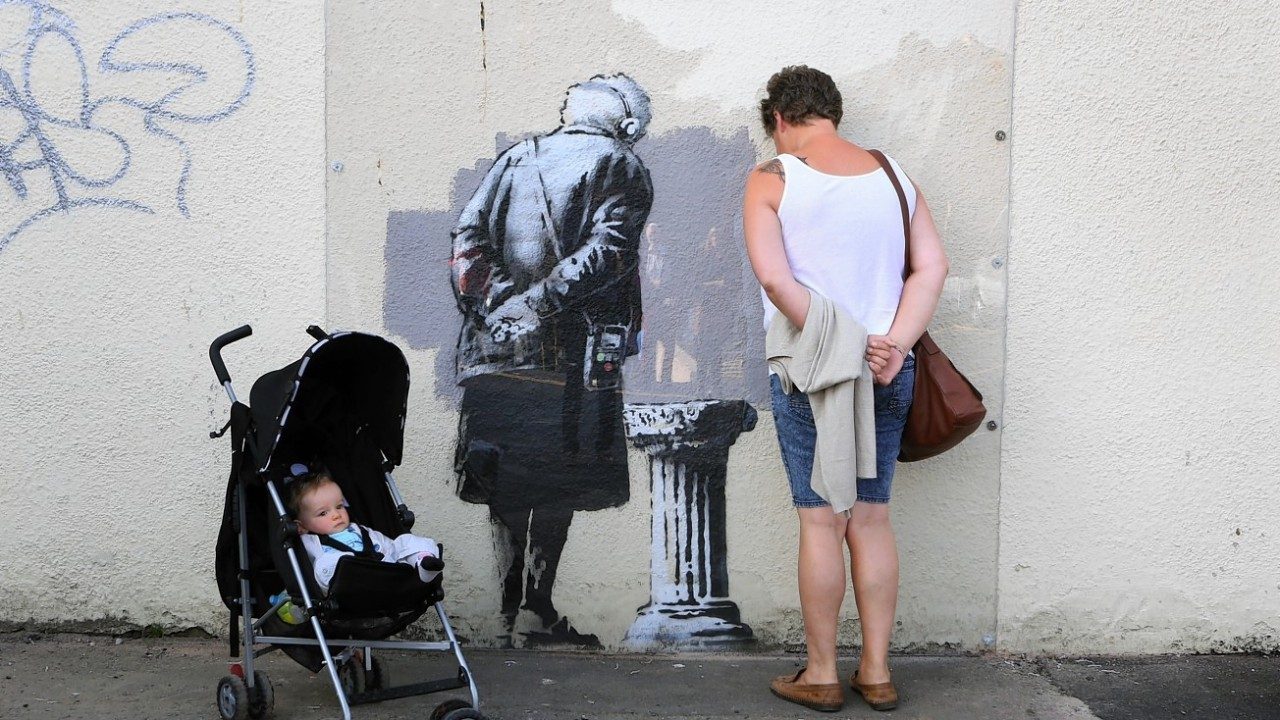 Local people view a mural called Art Buff created by street artist Banksy which appeared in Folkestone, Kent, during last weekend.