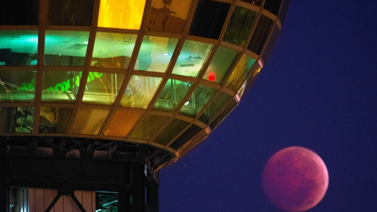 """The Earth's shadow is cast over the moon during a total lunar eclipse, as seen from beneath the Sunsphere in Knoxville, Tenn. Wednesday, Oct. 8, 2014. The red hue results from sunlight scattering off Earth's atmosphere, in what is known as a """"blood moon."""""""