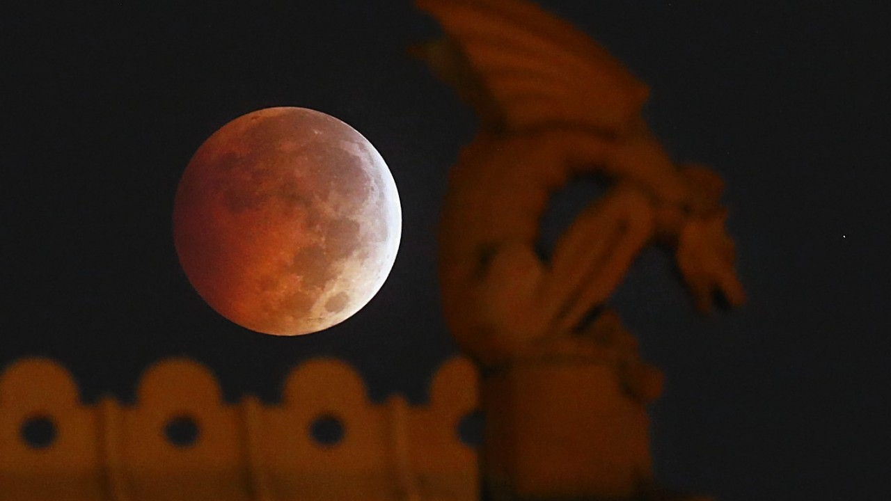 A lunar eclipse appears behind a gargoyle atop the old red Dallas County Courthouse early Wednesday morning, Oct. 8, 2014.  The moon appears orange or red, the result of sunlight scattering off Earth's atmosphere. This is known as the blood moon.