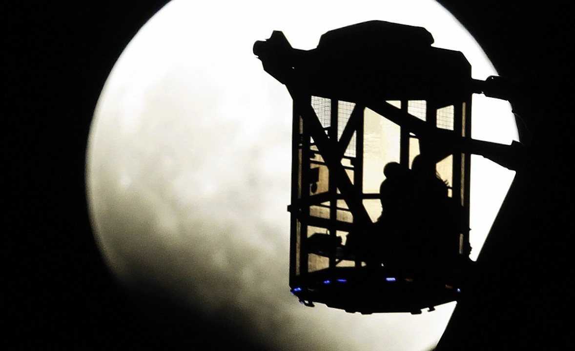 The Earth's shadow renders the moon as a couple in Ferris wheel observe it during a total lunar eclipse in Tokyo, Wednesday, Oct. 8, 2014.