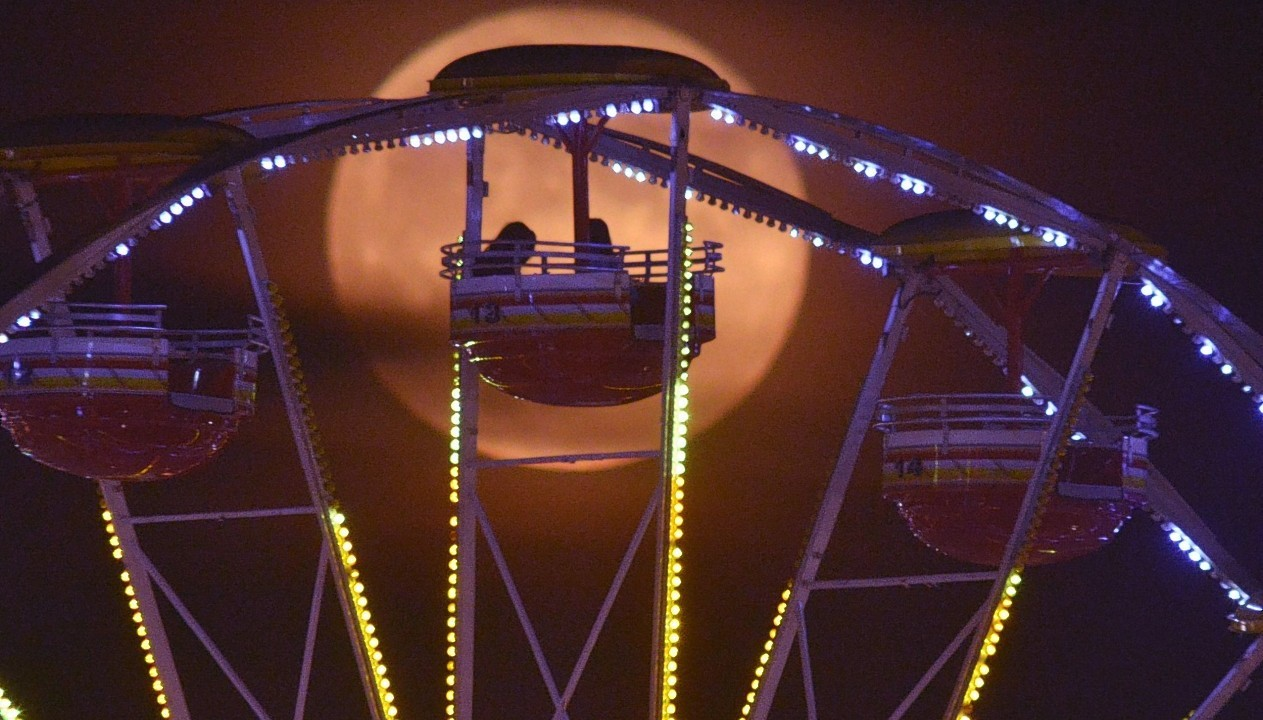 A full moon silhouettes riders at the 61st Annual Alabama National Fair in Montgomery, Ala., on Wednesday, Oct. 8, 2014.