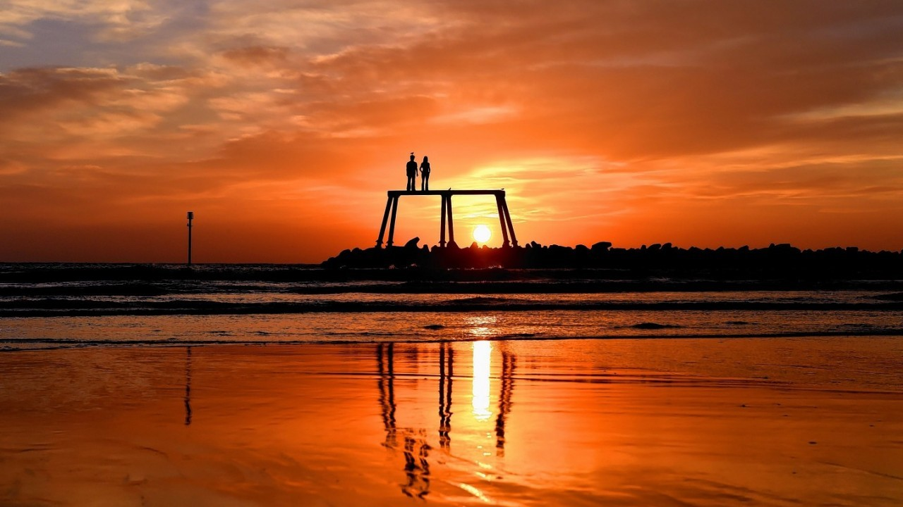 The Autumn sunrises over the north sea as The Couple by artist Sean Henery sits just of the coast at Newbiggin-by-the-Sea, Northumberland.