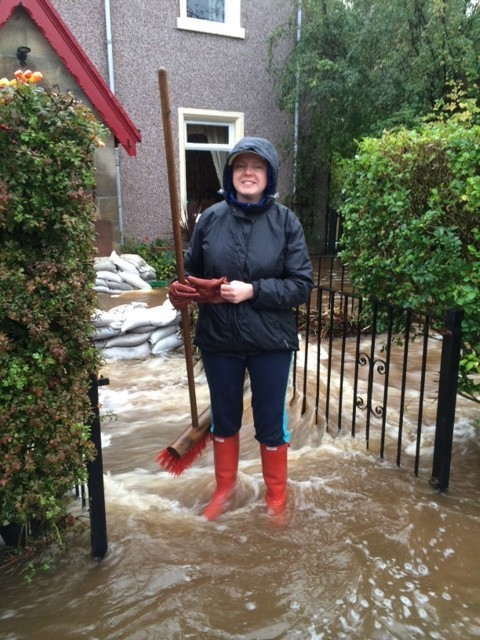 Evie Lumsden tries to keep flood waters from her mother's home on Millburn Road