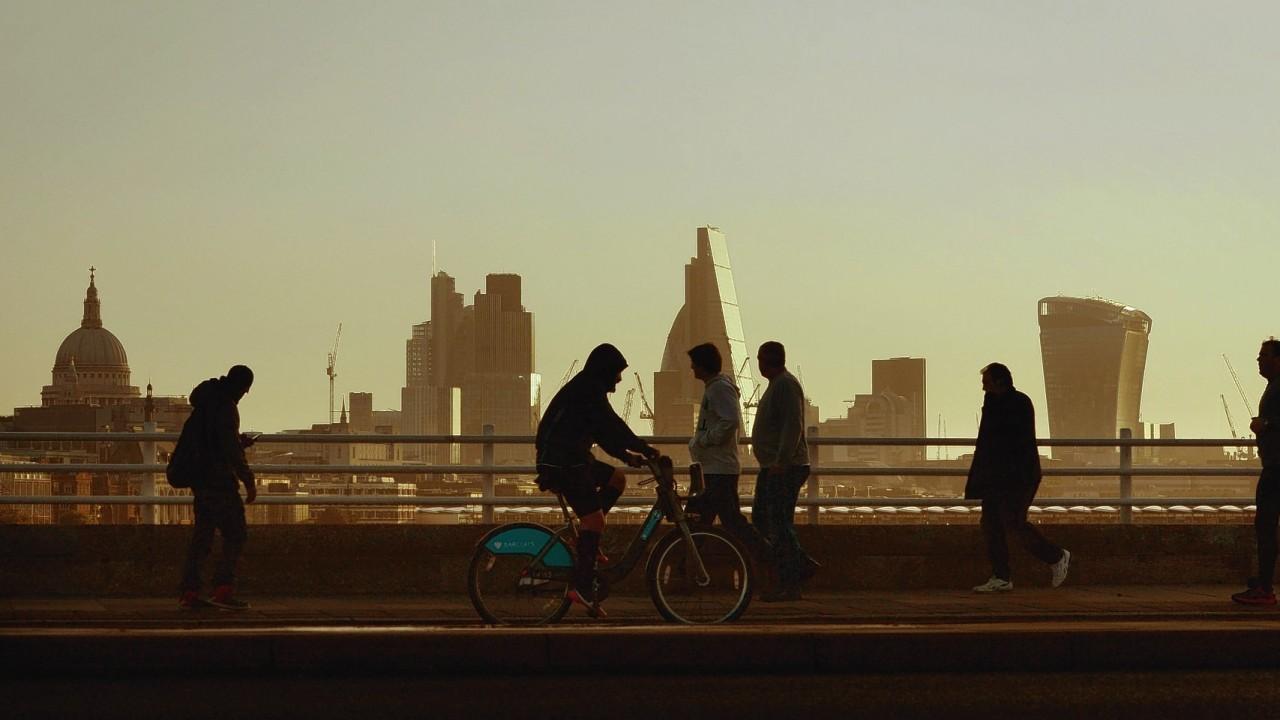 Early morning commuters cross Waterloo Bridge in London, as the sun rises.