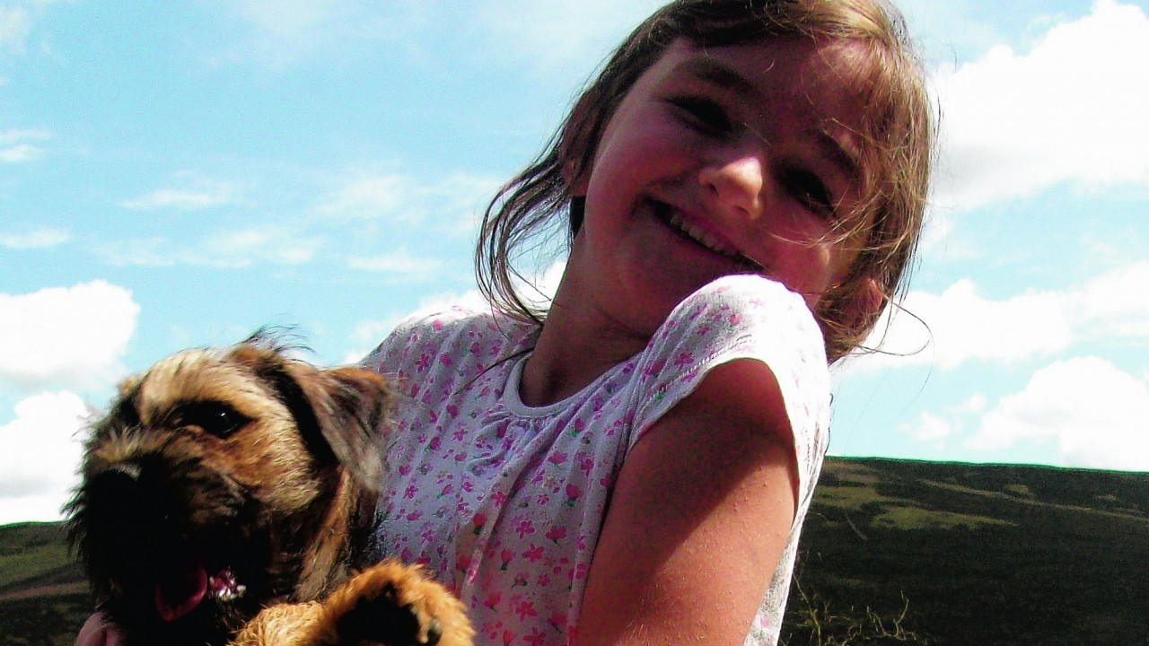 Border terrier Brodie who lives with Bob and Sheila Fraser in Letham, Angus, pictured  with their granddaughter Grace while visiting the Backwater Reservoir, Lintrathen.