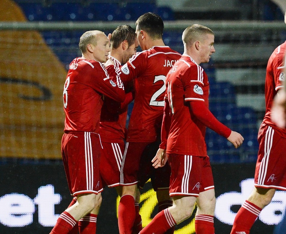 The Dons players celebrate the only goal of the game
