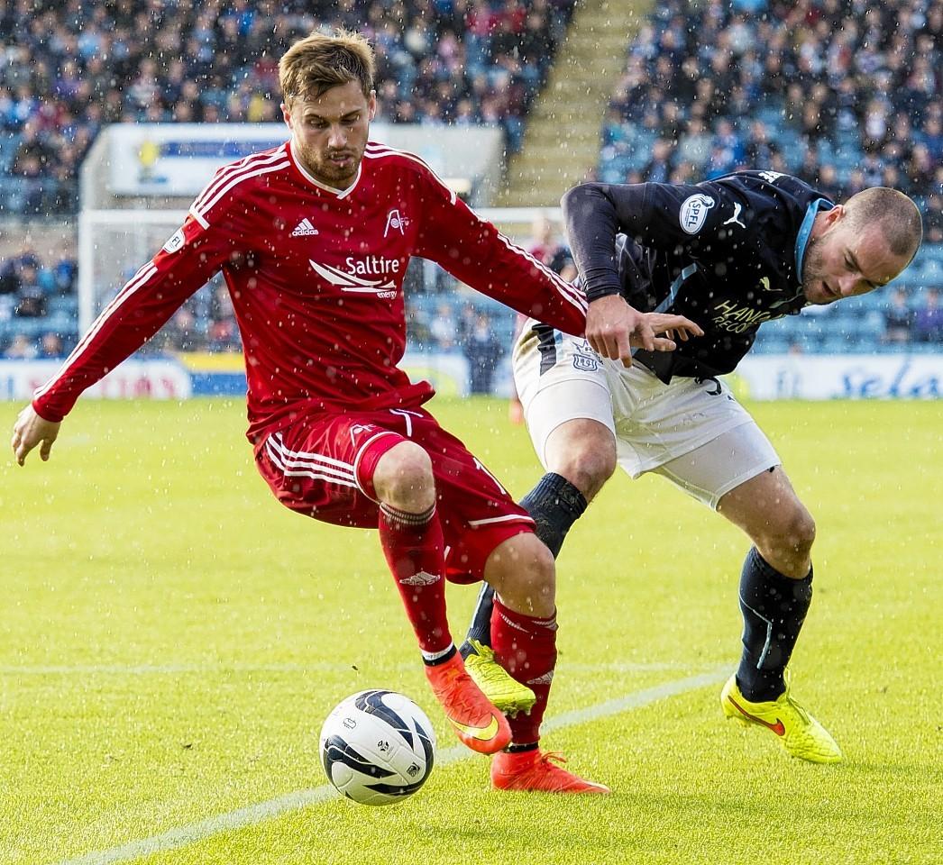 Dundee defender James McPake challenges Dons striker David Goodwillie.