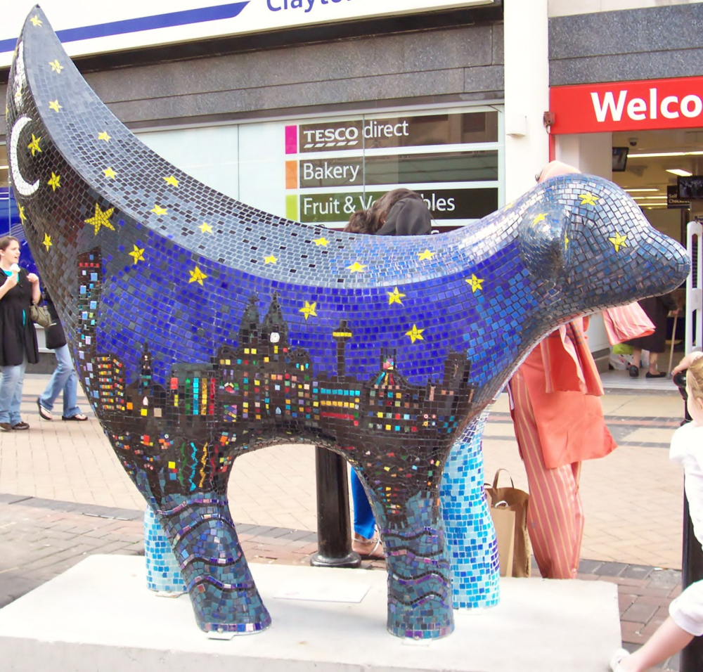 Artist Debbie Ryan's community sculpture in Liverpool reflects the city's waterfront at night and day on either side of the canine creation.