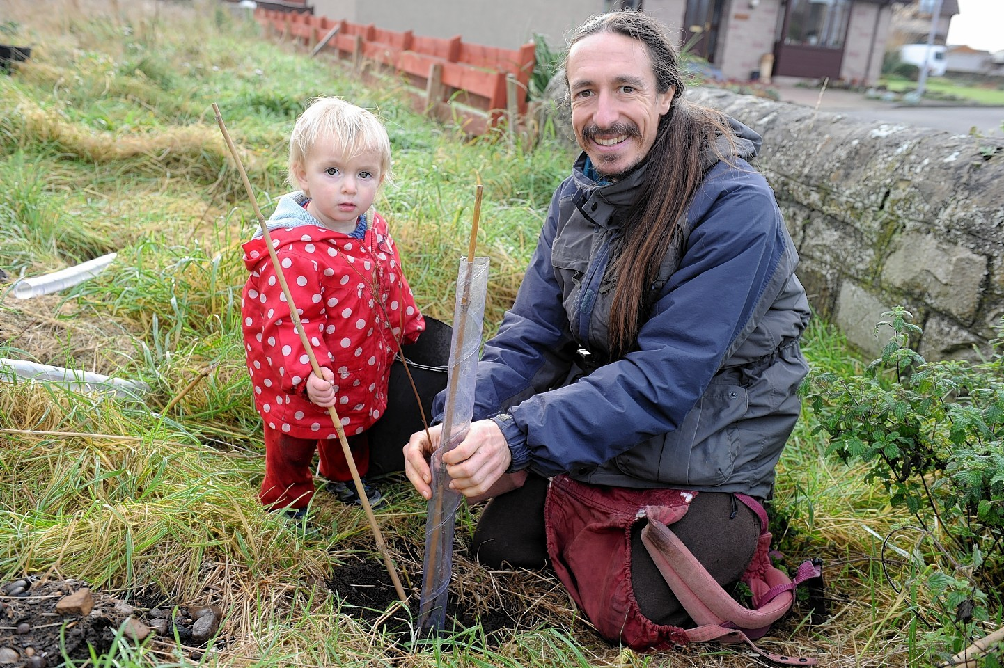 A Burghead family planting a tree on the community garden site