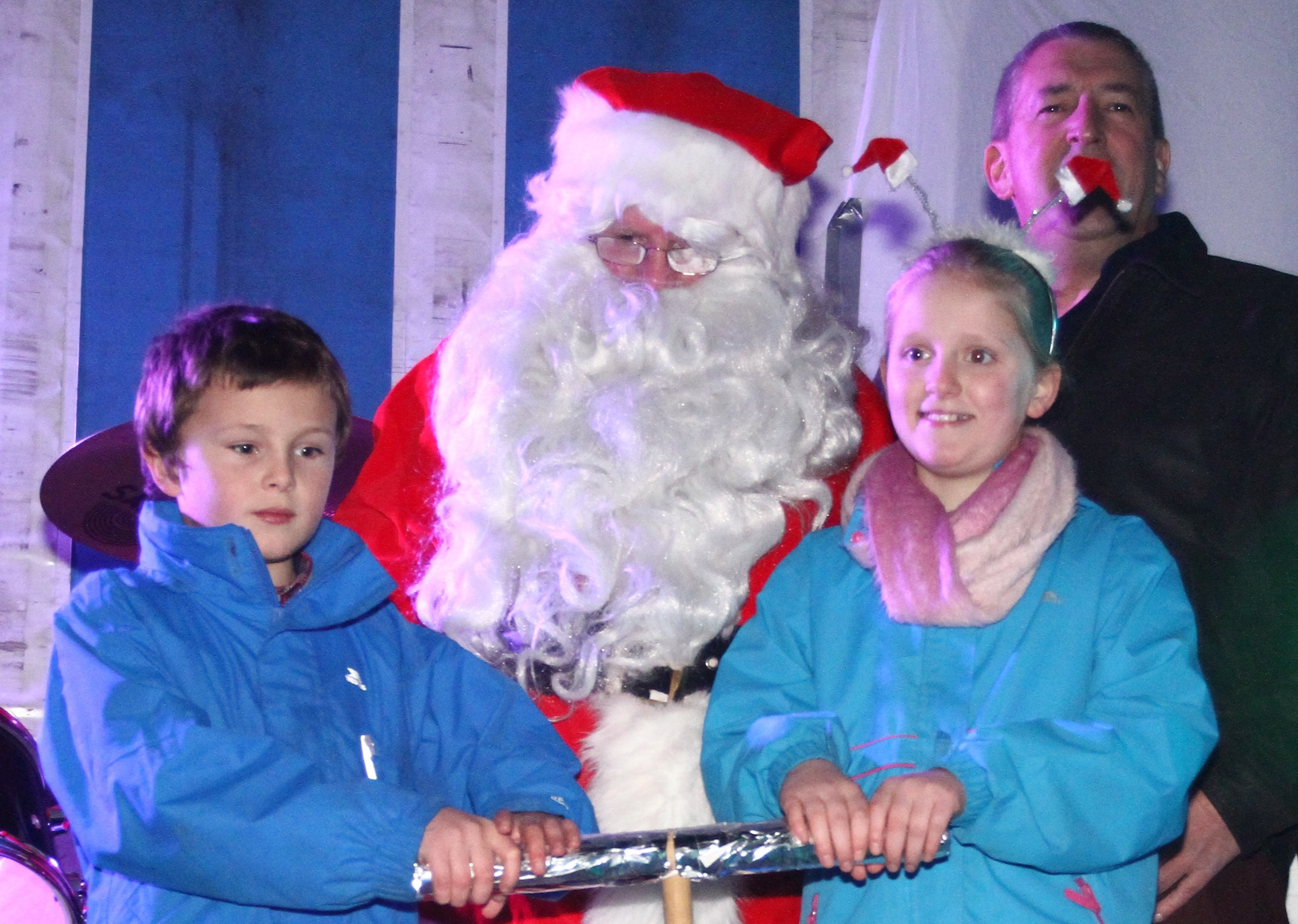 Santa keeps an eye on Logan Watson (left) and Iona Keyes with Graeme Bass Chair of Bid4Oban as they push the plunger to switch on the Christmas lights in Oban as part of the Reindeer Parade.