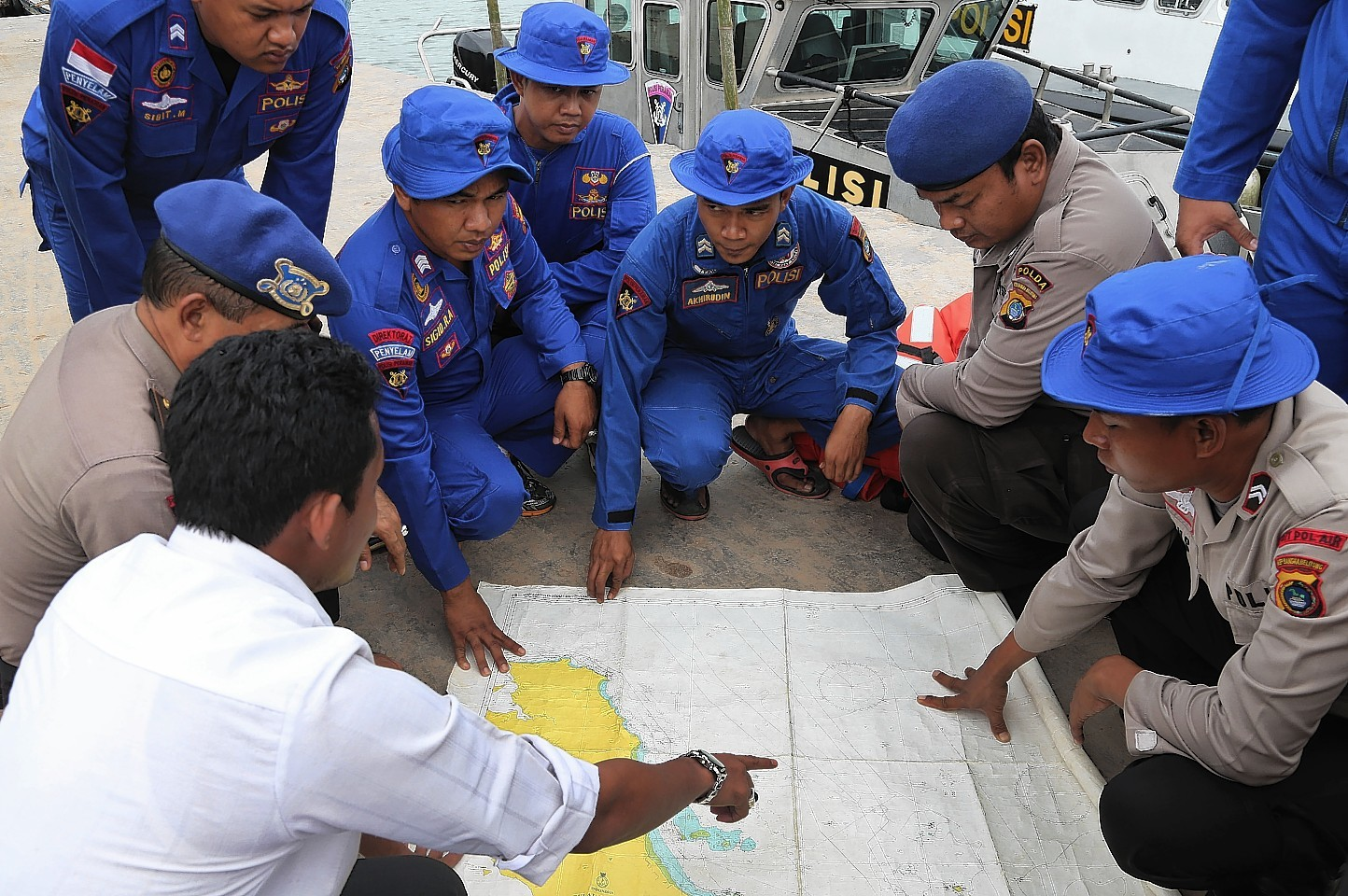 Members of Indonesia's Marine Police hold a briefing on board a search and rescue craft prior to their heading out to sea to search for the missing AirAsia flight QZ8501