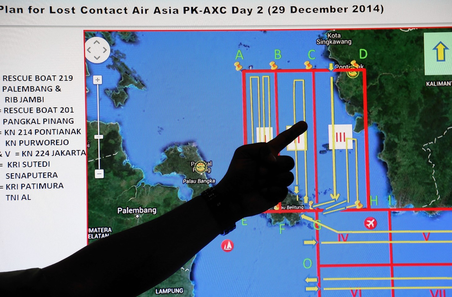 A member of the Indonesian National Search and Rescue Agency (BASARNAS) points to a map of a search area during a briefing prior to a search and rescue operation of the missing AirAsia flight QZ8501