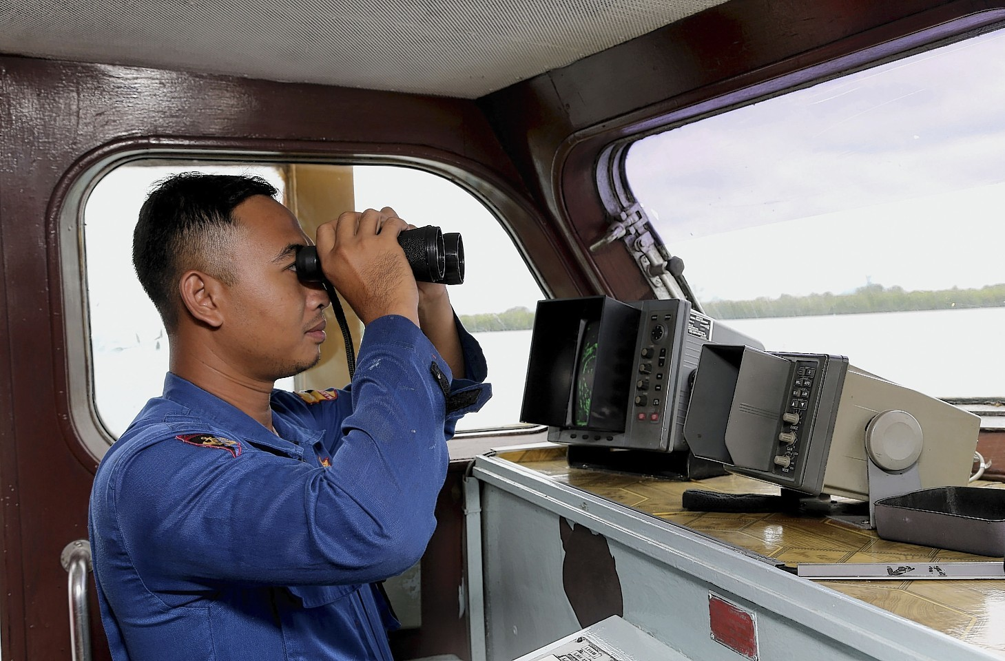 An Indonesian Marine Policeman checks his surroundings from his search and rescue crafts as he and his crew members prepare a search operation for the missing AirAsia flight QZ8501