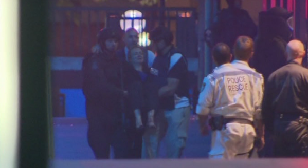 A girl is carried from the cafe by police