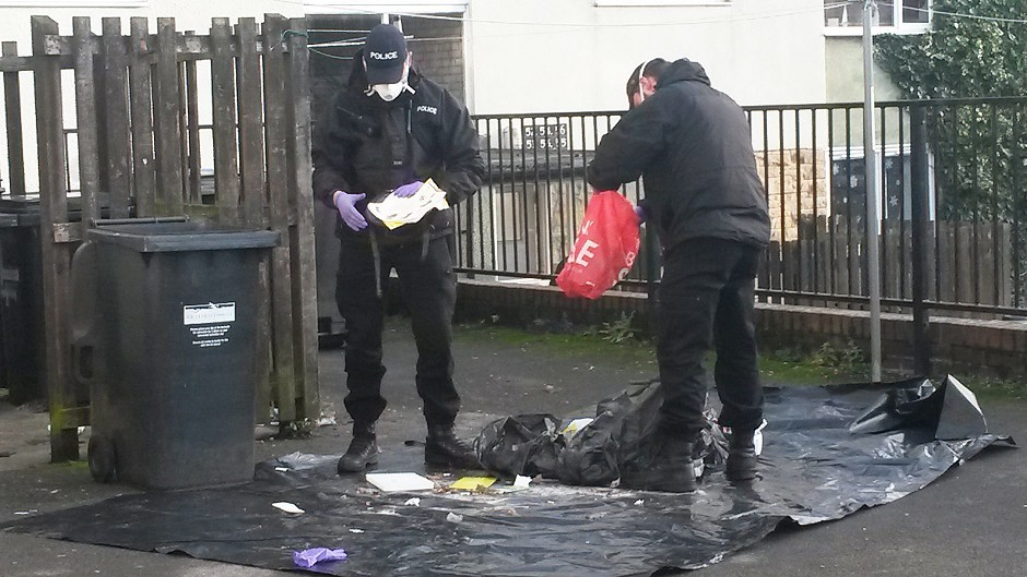 Police carry out a search of the bins on a small housing estate in Richmond, North Yorkshire, where a newborn baby girl's body was found in a wheelie bin