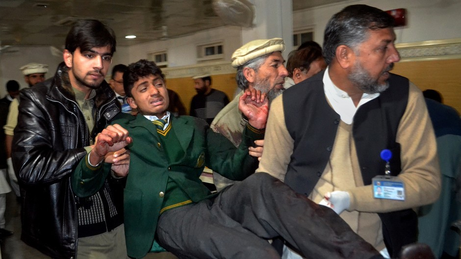 Pakistani volunteers carry a student injured in the shootout at a military school attacked by the Taliban in Pakistan