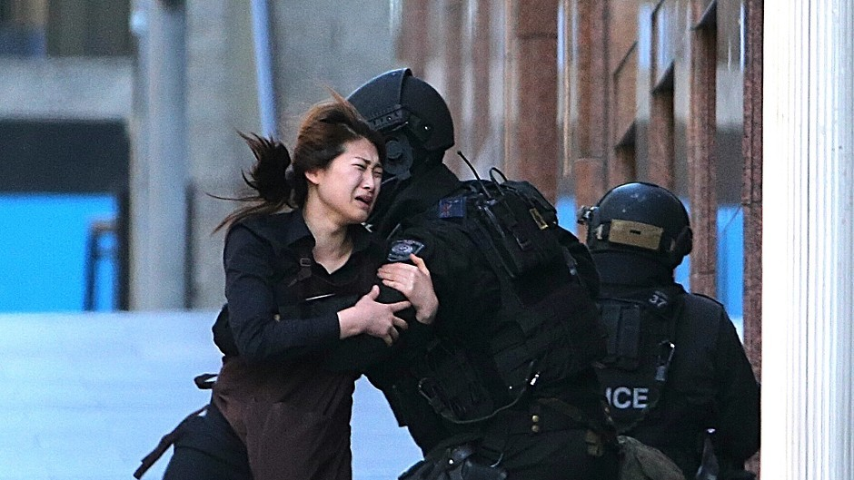 A hostage runs to armed tactical response officers after escaping from a cafe under siege at Martin Place in the central business district of Sydney (AP)