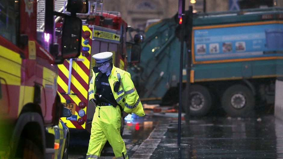 A police officer at the scene of the bin lorry crash in Glasgow. The lorry can be seen in the background.