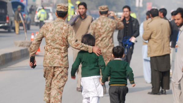 Children escorted from the scene in Pakistan