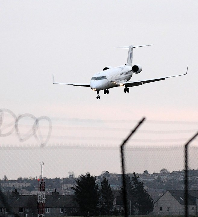 A plane approaches Aberdeen Airport runway in difficult weather