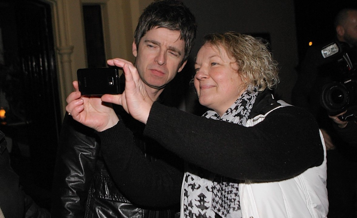 Noel Gallagher poses for a picture outside the hotel