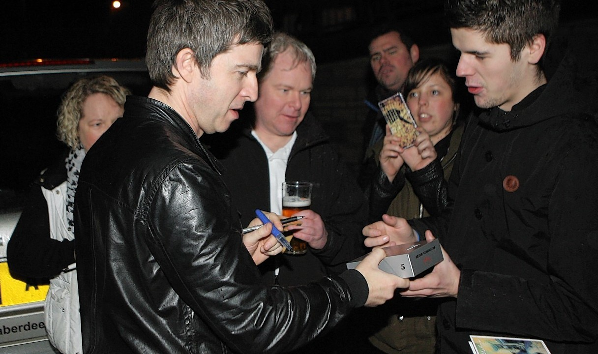 Noel Gallagher signs autographs outside the hotel