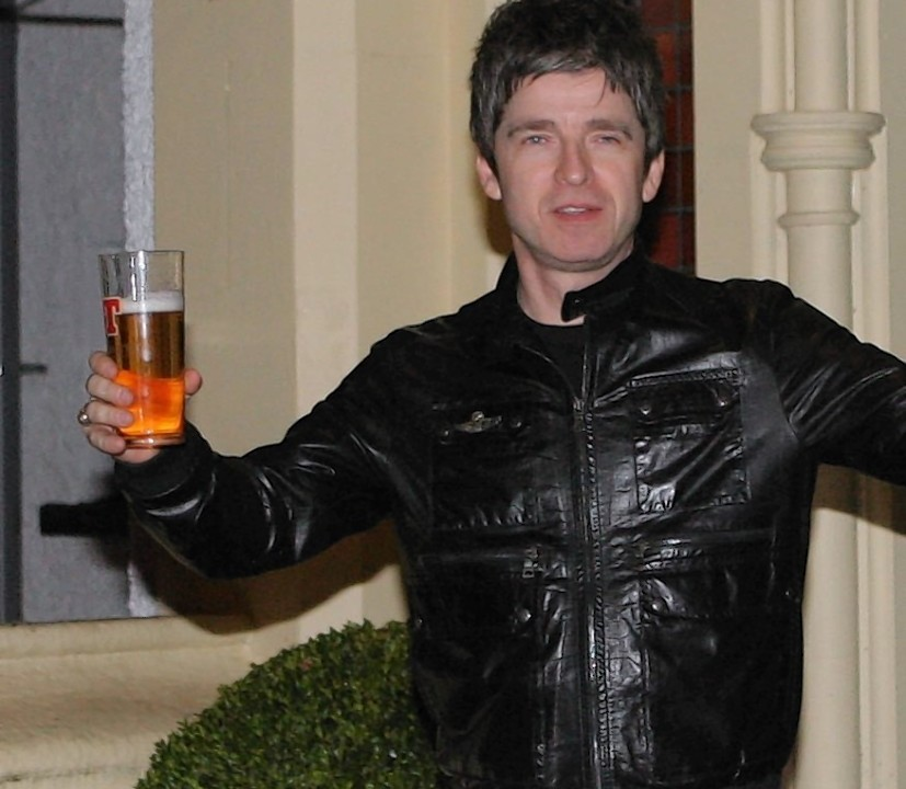Noel Gallagher arrives to sign autographs outside the hotel, pint in hand