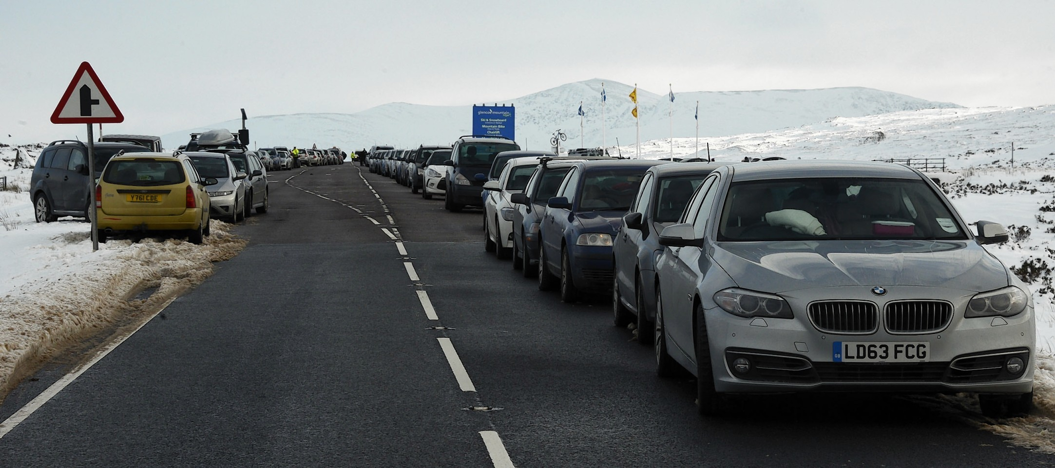 Cars line the busy A82 at Glencoe Mountain Resort .