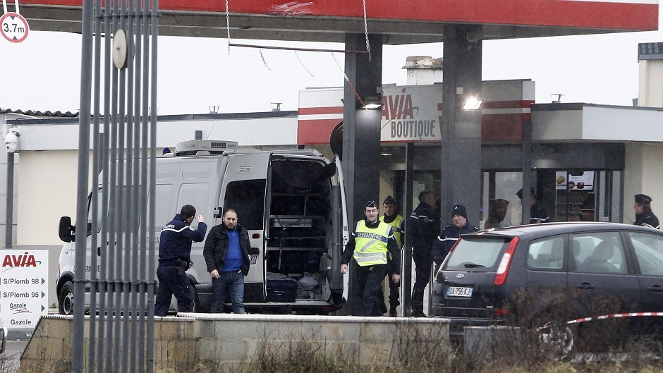 Police officers investigate a petrol station in Villers Cotterets, 80 kilometres north east of Paris, where the suspects were reportedly spotted (AP)