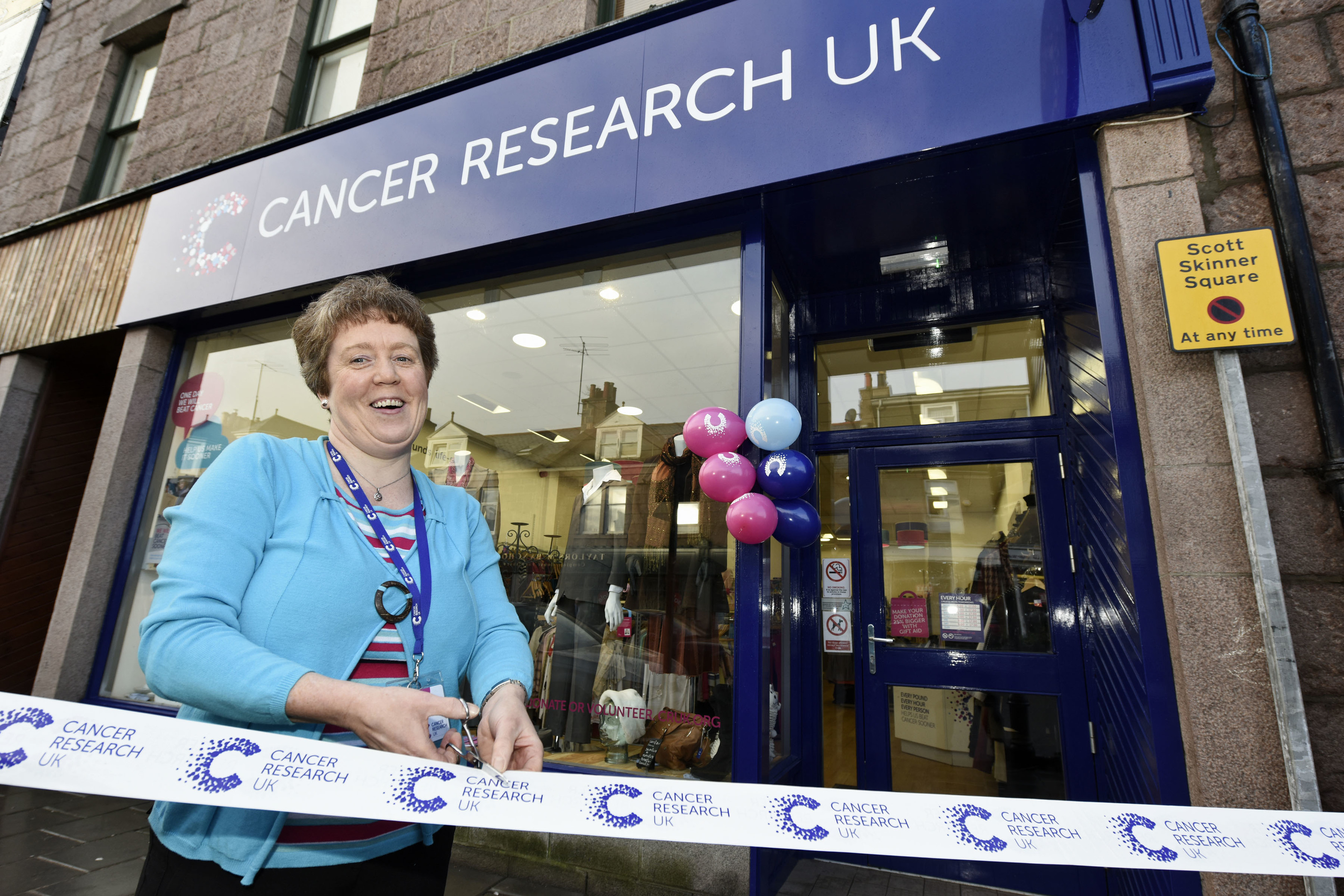 Yvonne Thomson, new manager of Cancer Research UK shop in Banchory cuts the ribbon