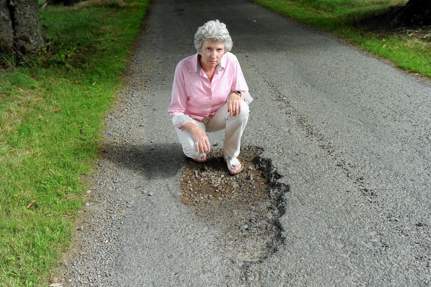 Council convener Isobel McCallum inspects a Highland pot hole.