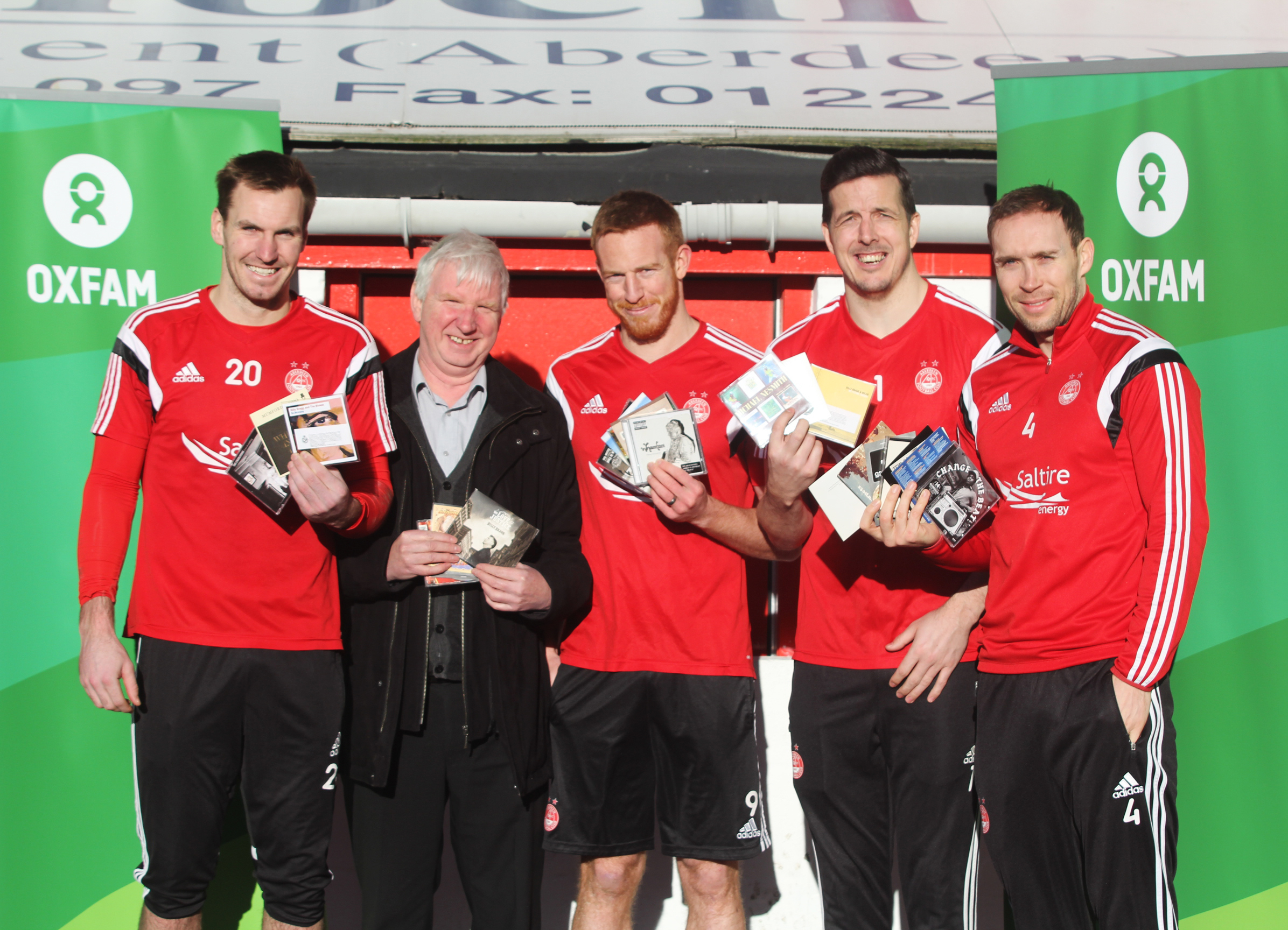 Oxfam Area Manager Peter Roy, with Dons players Scott Brown, Adam Rooney, Jamie Langfield and Russell Anderson.