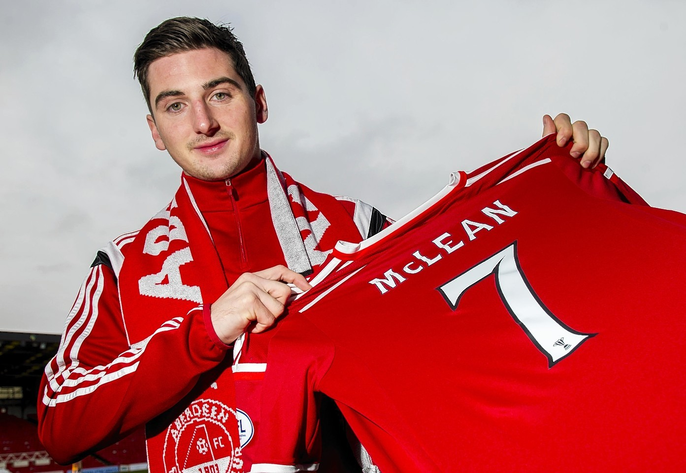 Kenny McLean proudly displays his Dons top