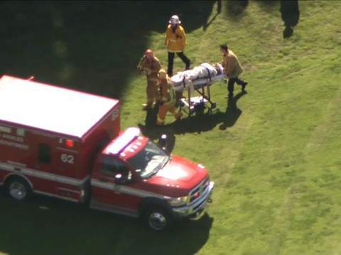 A person, believed to be Ford, is wheeled away on a stretcher