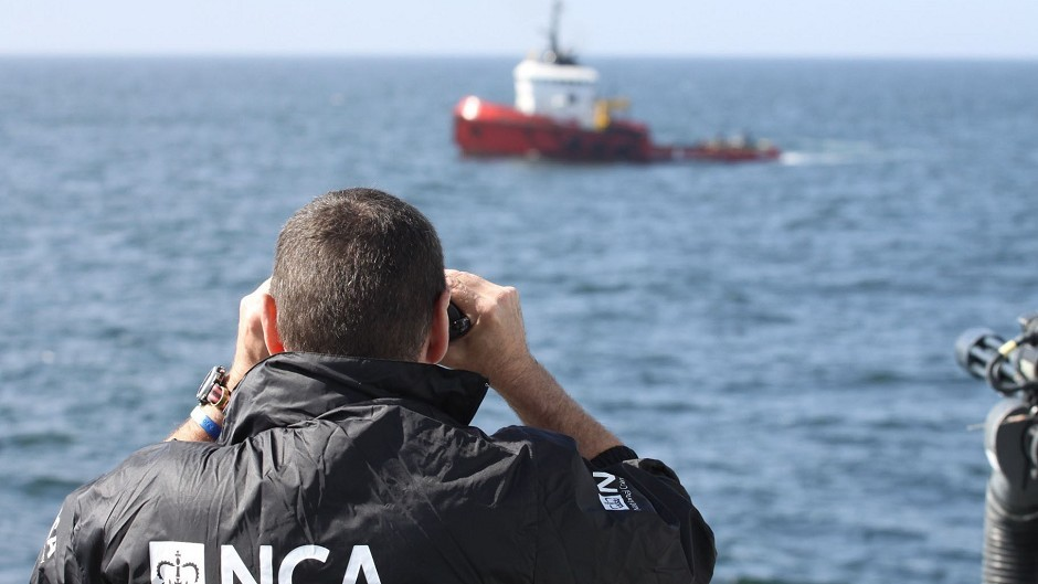 The MV Hamal being watched by an NCA officer as it was intercepted by the frigate HMS Somerset and Border Force cutter Valiant (PA/National Crime Agency)