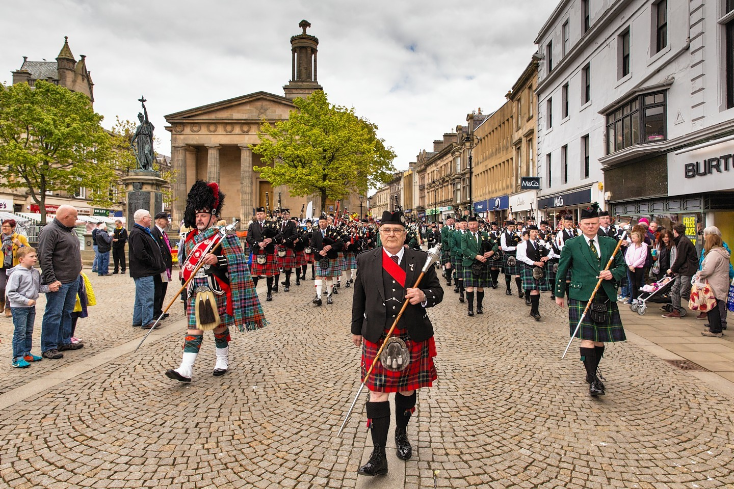 The massed bands of Elgin and District, Ullapool and District, Strathisla and Huntly and District marching along the High Street in Elgin