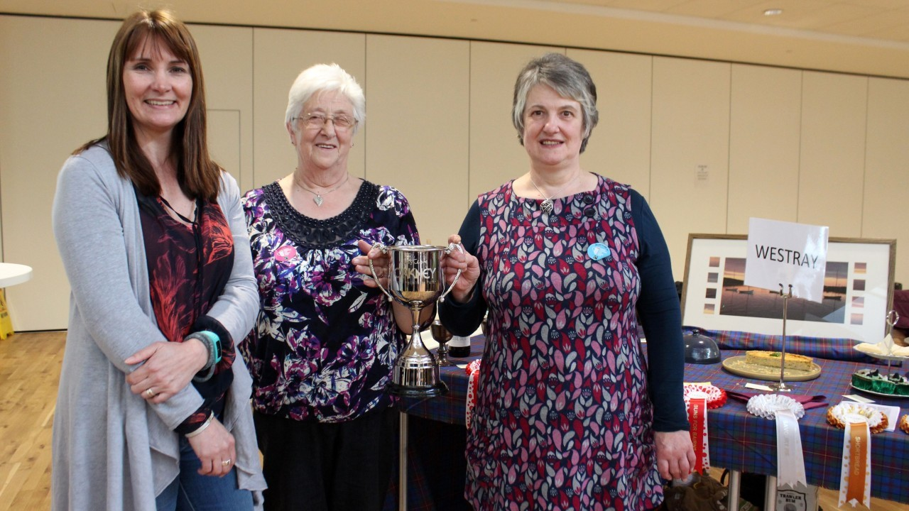 Westray representatives Ena Fergus (left) and Netta Harcus (right), receiving the Homemade in the Parish cup from OFD's Fiona MacInnes (far left)