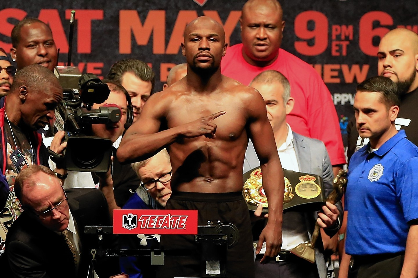 Floyd Mayweather Jr. poses on the scale during his official weigh-in