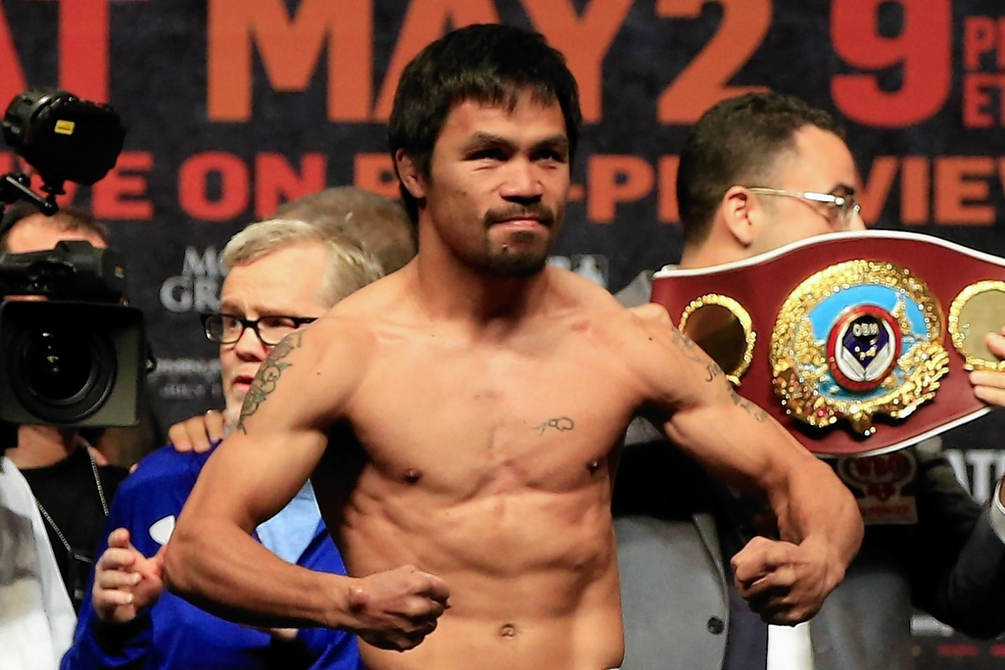 Manny Pacquiao poses on the scale during his official weigh-in