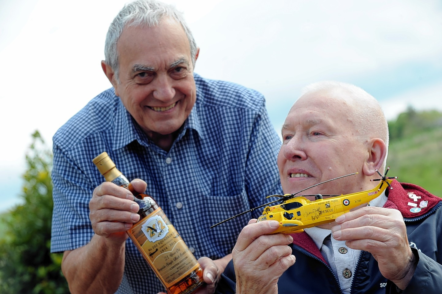 Rob Matthews with the Seaking model he's donating to Mrayvia to be auctioned and Bob Pountney with the bottle of 202 Squadron whisky, also to be auctioned. Picture by Gordon Lennox