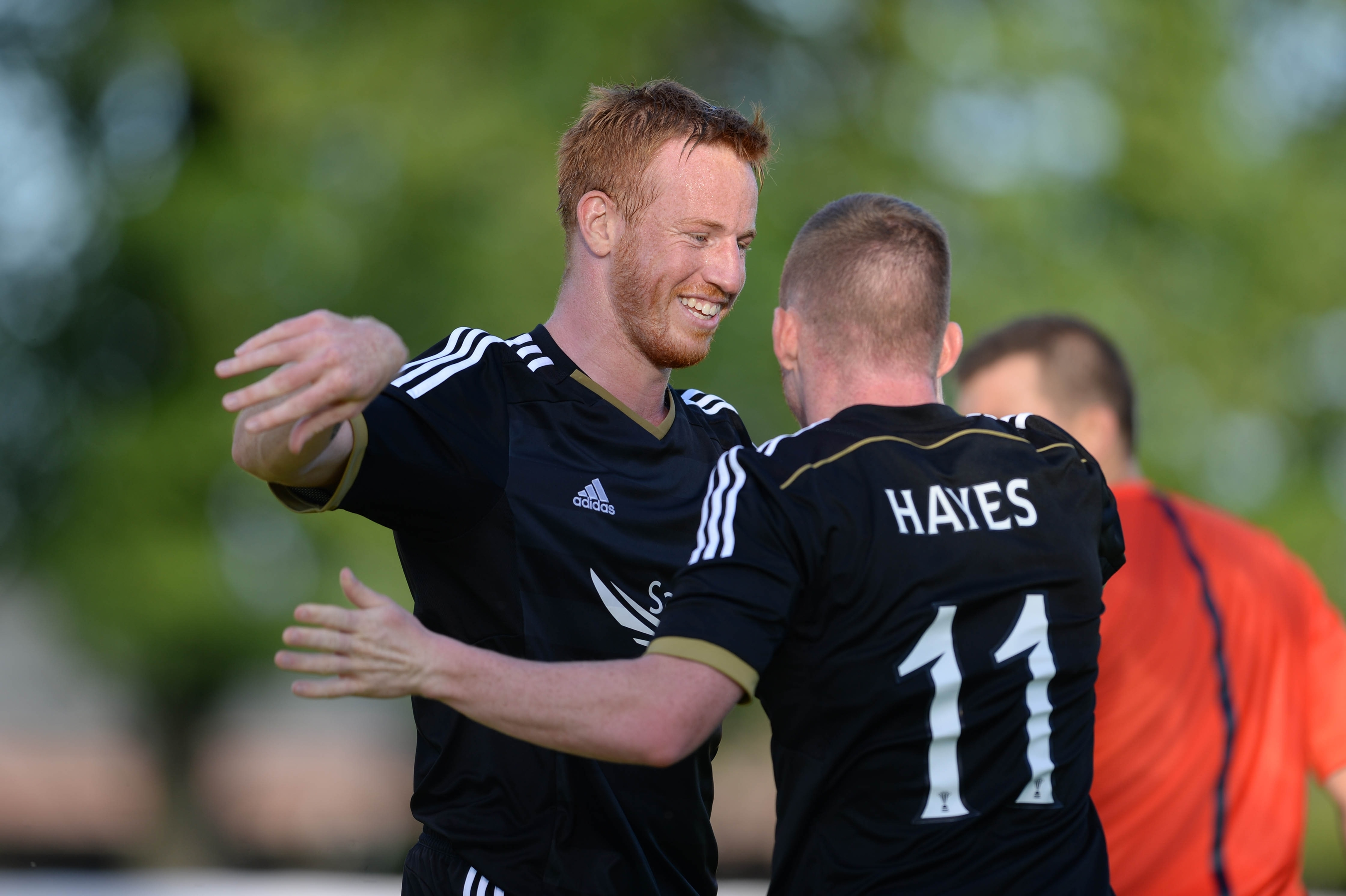 Adam Rooney celebrates a goal with former Dons team-mate Jonny Hayes