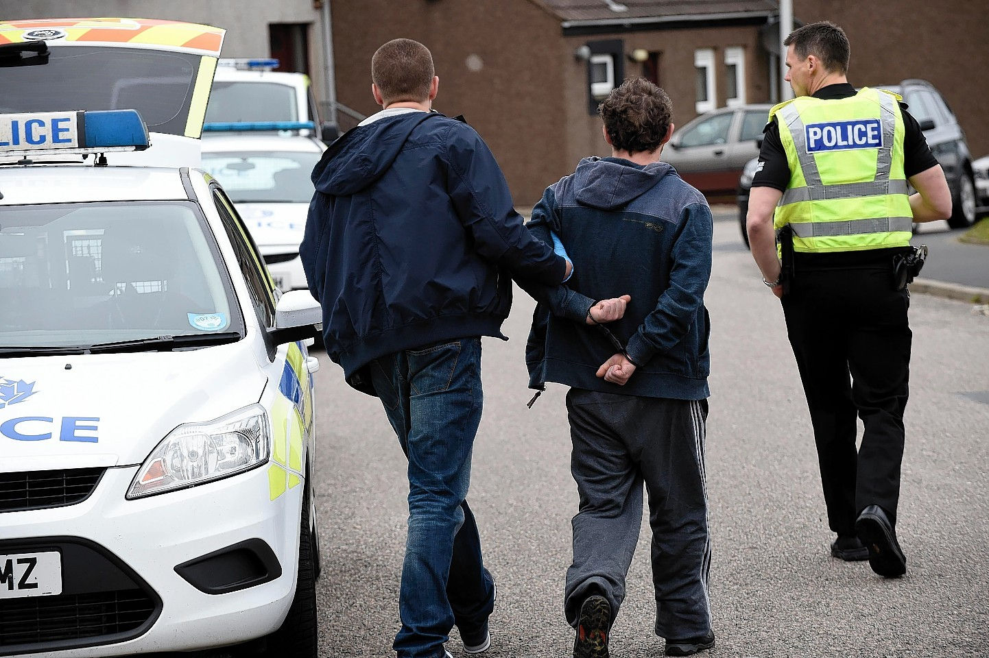 A man is taken away from Scalloway Park during the raids