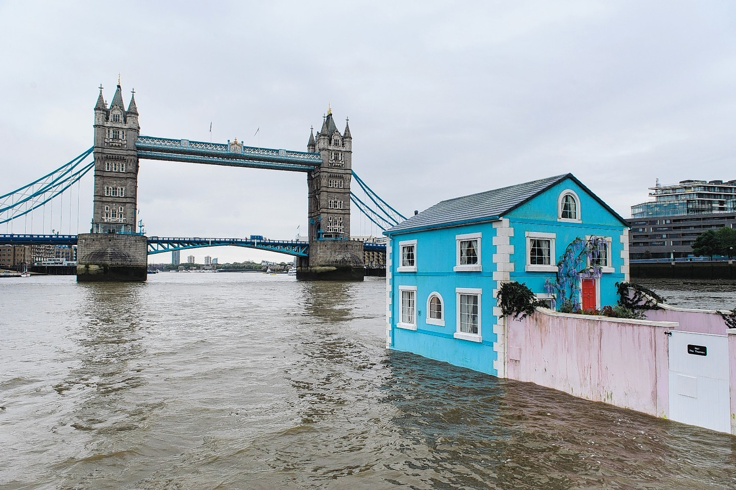 A fully functioning floating house passes Tower Bridge as it travels up the River Thames.