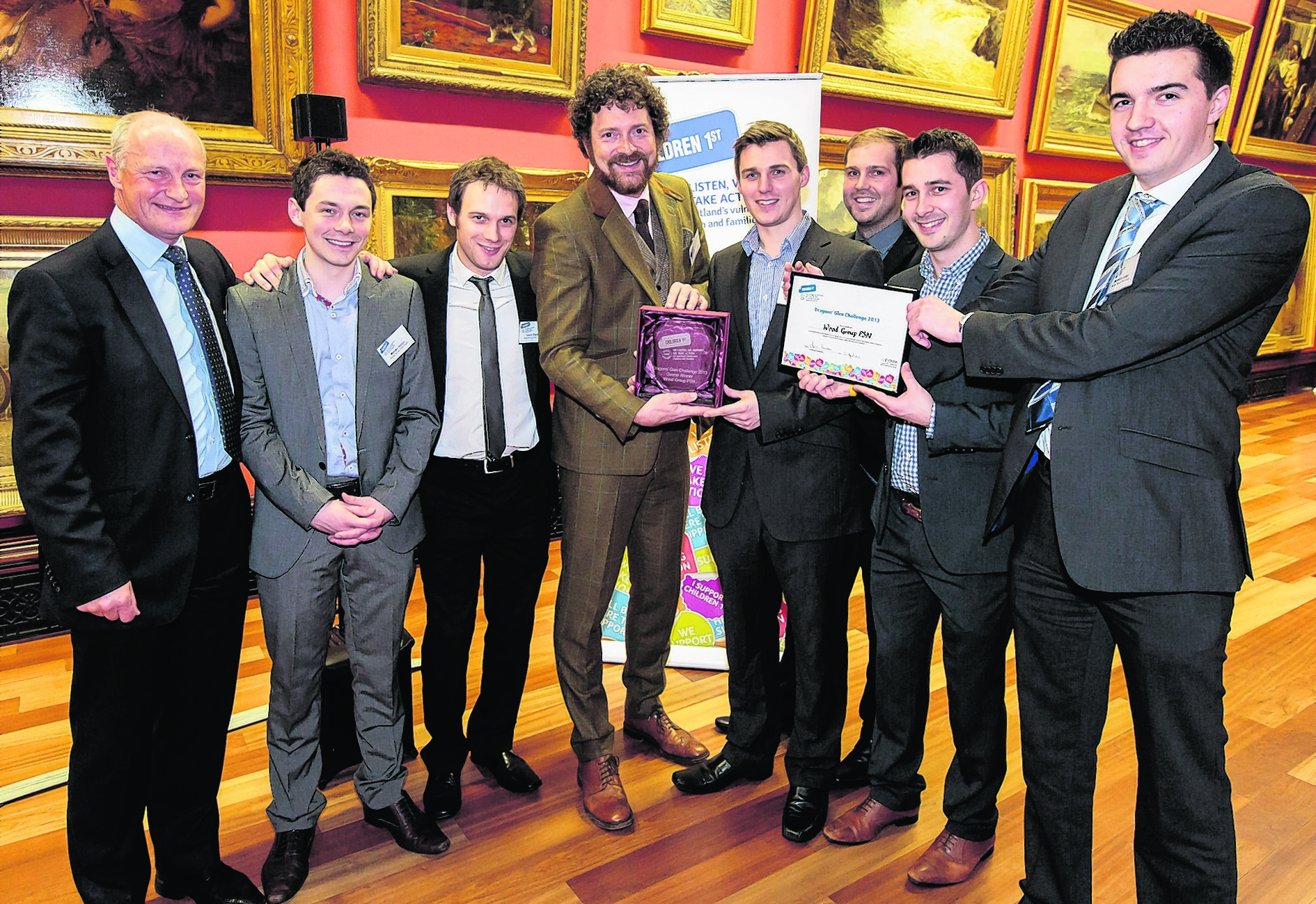 Chris van der Kuyl, Dundee Dragon and Chairman of 4J Studios, presents the Most Money Raised Award trophy and framed certificate to the winning team, Wood Group PSN, who raised £21,468.58 by selling a desk calendar. Pic: ASM Media & PR