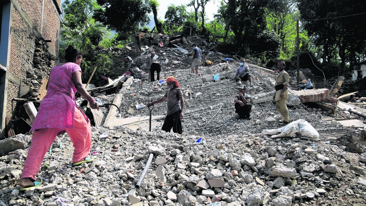 Nepali people collect usable belongings amid the debris of destroyed houses at Lamosangu village in Sindhupalchowk, Nepal after the 7.8-magnitude earthquake