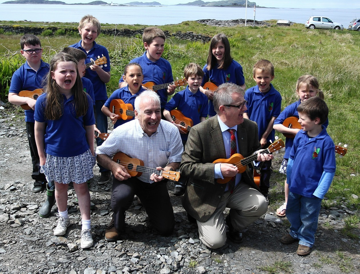 Brendan O'Hara MP for Argyll and Bute (left)  performs his first official task since he has been elected to parliament by helping the Trustees and Children of Luing Primary School unveil the Fladda Light