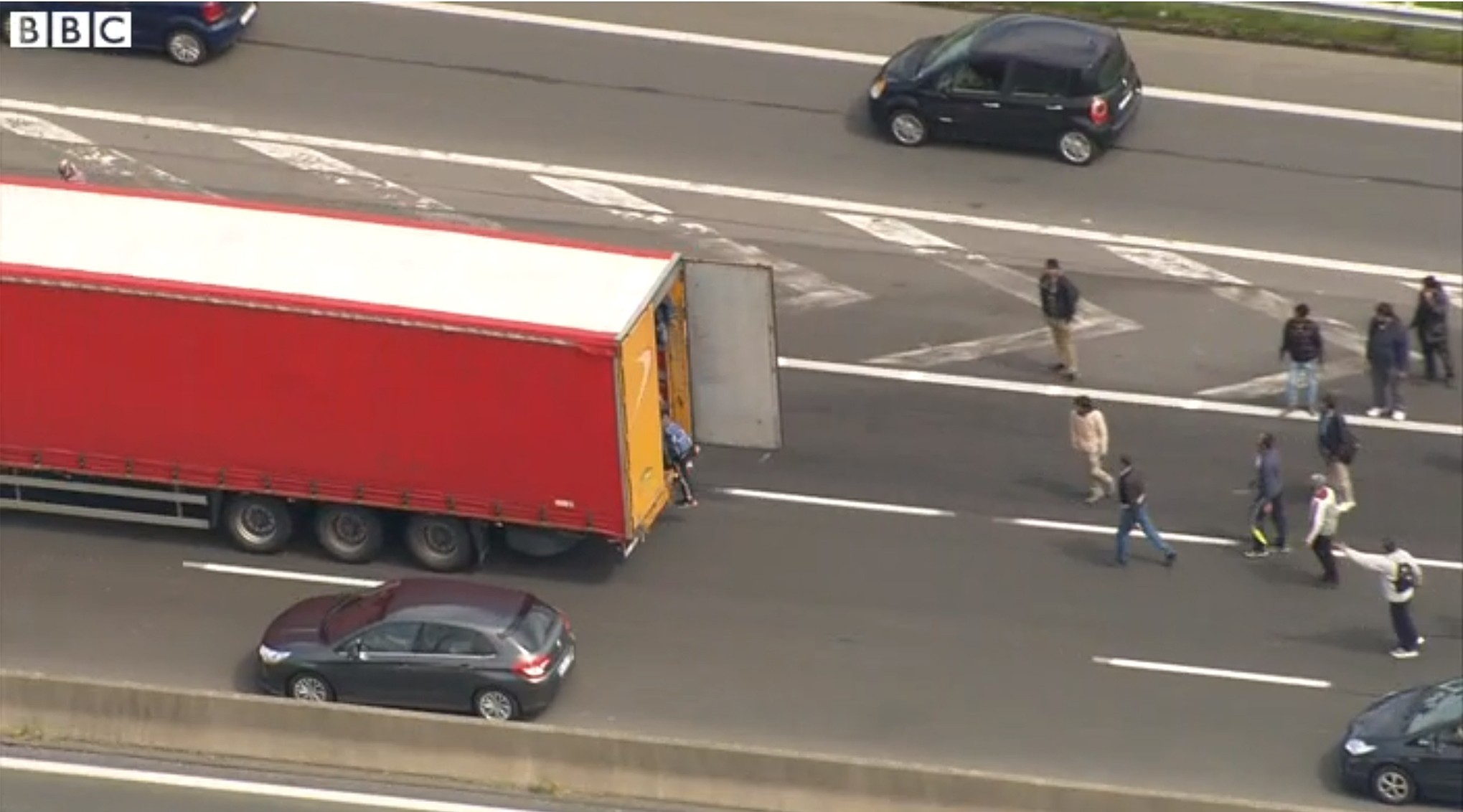 Migrants by the side of a road in Calais attempting to board a lorry as French ferry workers strike. Picture from BBC News.