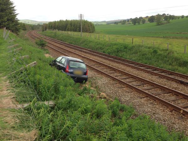 The car appears to have almost crashed onto the rail tracks