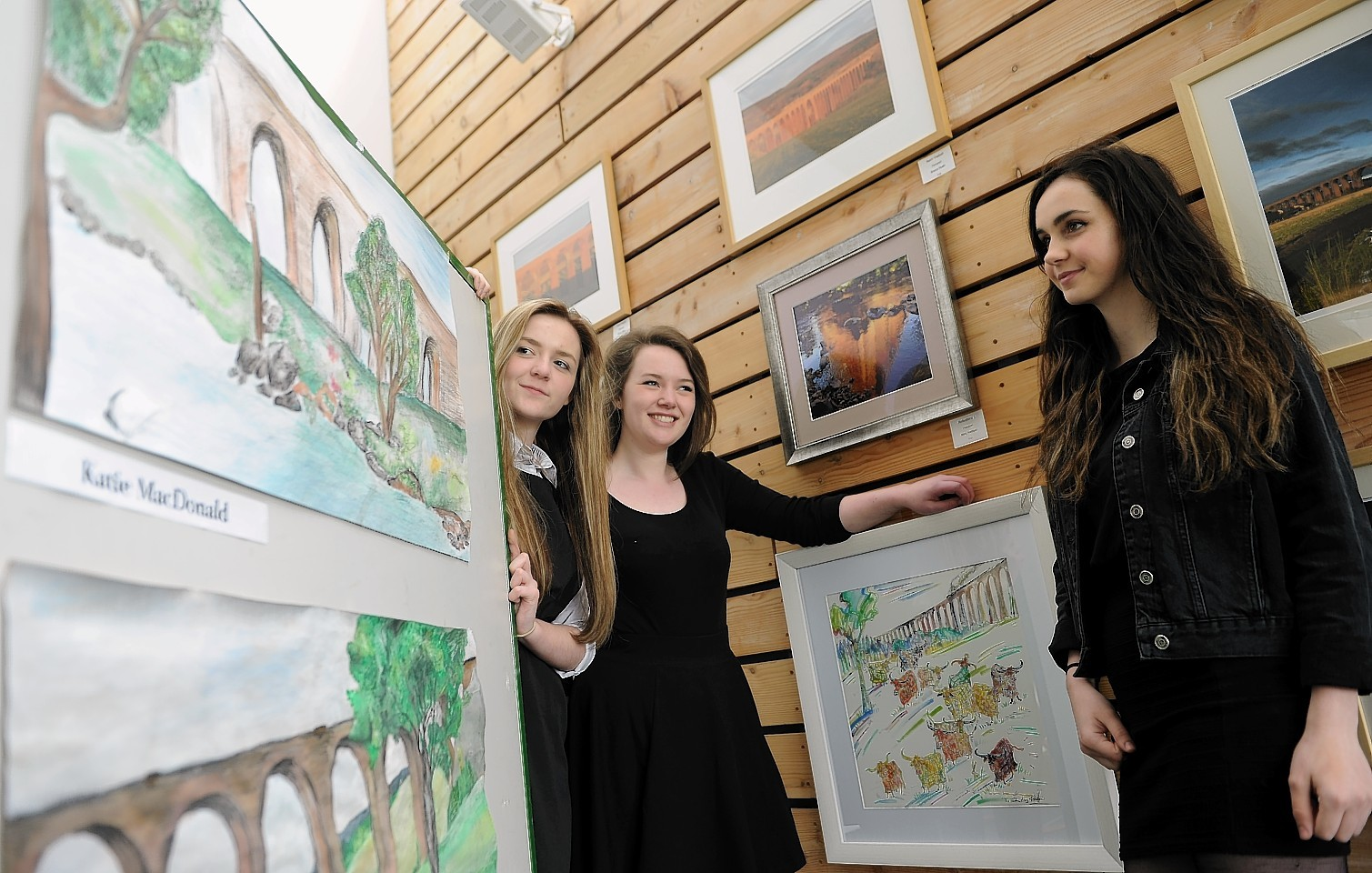 Pupils of Culloden Academy (L-R) Chelsea MacGillivray, Katie MacDonald and Susie Hay with some of their works and that of other artists on show at the Culloden Visitor Centre following an art project on the Culloden Viaduct.