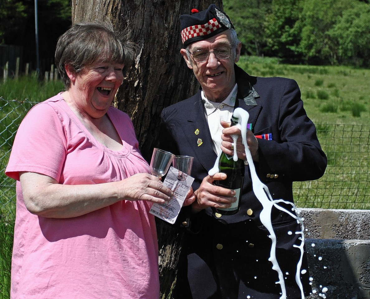 Betty and Geordie Rhodick crack open the champagne after winning on the lottery